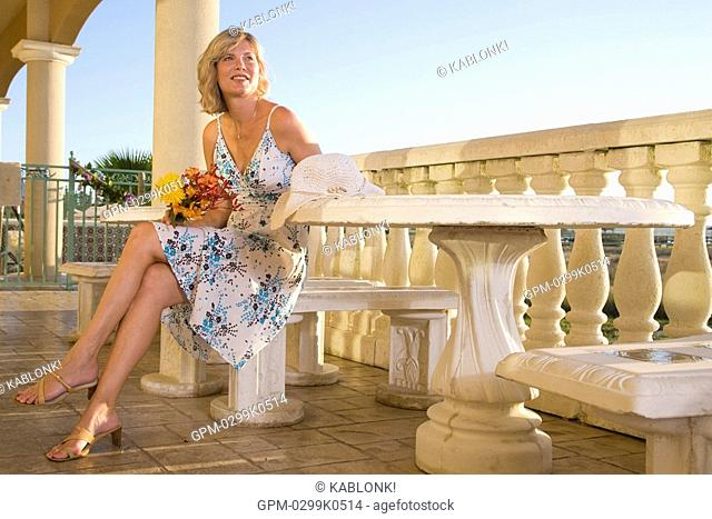 Young woman sitting at table on balcony