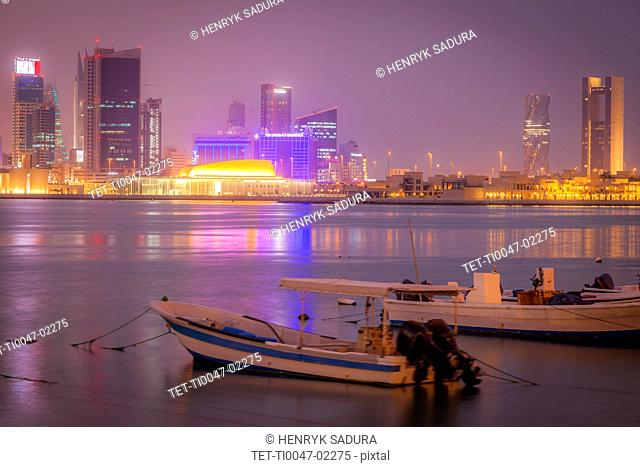 Moored motorboats by city skyline at night in Manama, Bahrain