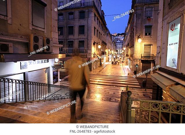 Rear view of man walking downstairs, Chiado, Rua Aurea, Rua Santa Justa, Baxia, Lisbon, Portugal