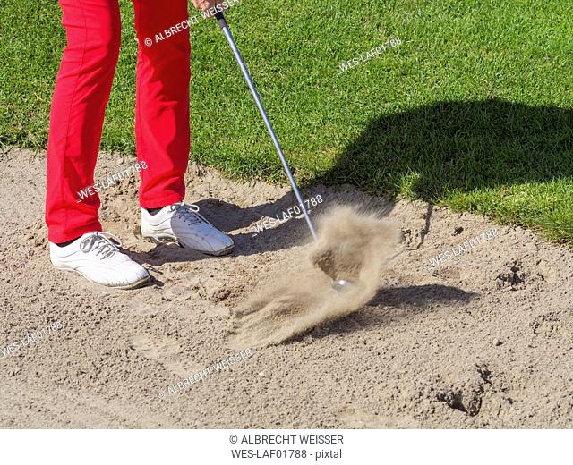 Golfer playing bunker shot, partial view