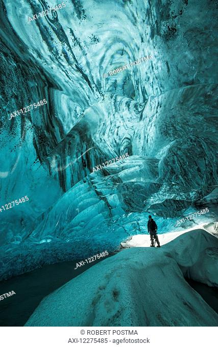Person standing under the Vatnajorkull ice cap in a large ice cave; Iceland