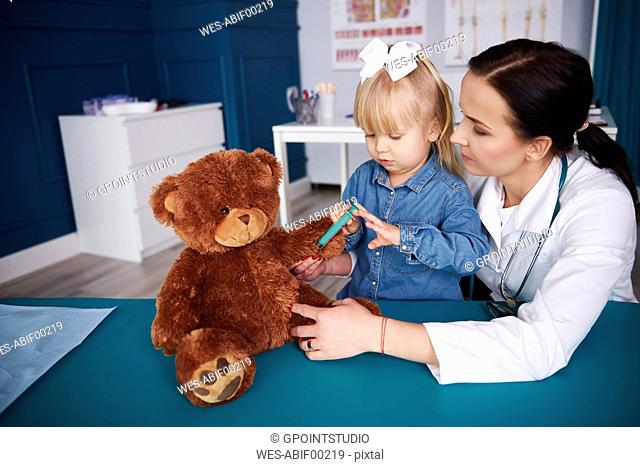 Doctor and girl vaccinating teddy in medical practice