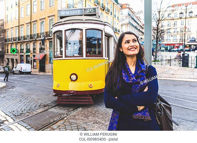 Woman in street by tram, Lisbon, Portugal