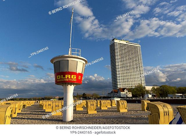 beach at the Baltic Sea with beach chairs, lifeguard tower and high rise hotel, Travemünde, Schleswig-Holstein, Germany