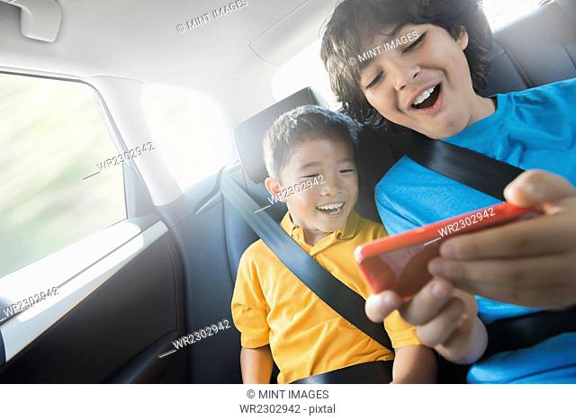 Two children travelling in the back seat of a car sharing a handheld games tablet