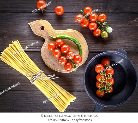 long yellow raw spaghetti and red cherry tomatoes on a brown wooden table, top view