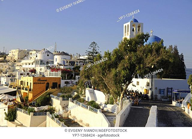 Thira the capital town of Santorinin island with blue domed chapel and bell tower at sunset