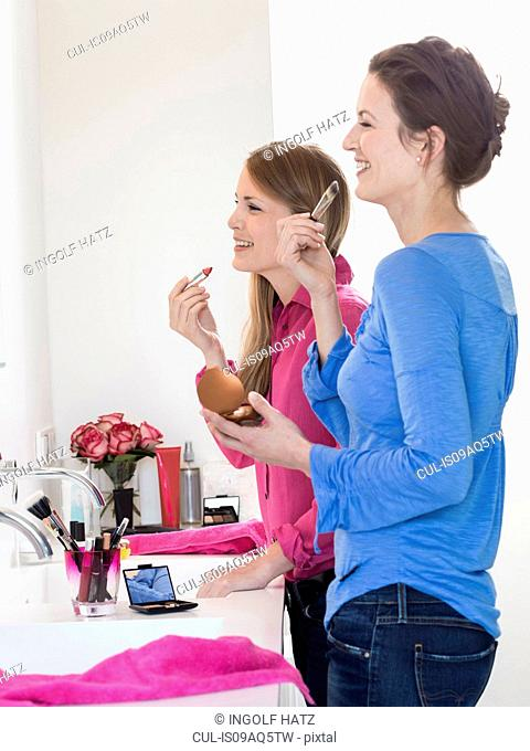 Two female friends gossiping and applying lipstick in bathroom