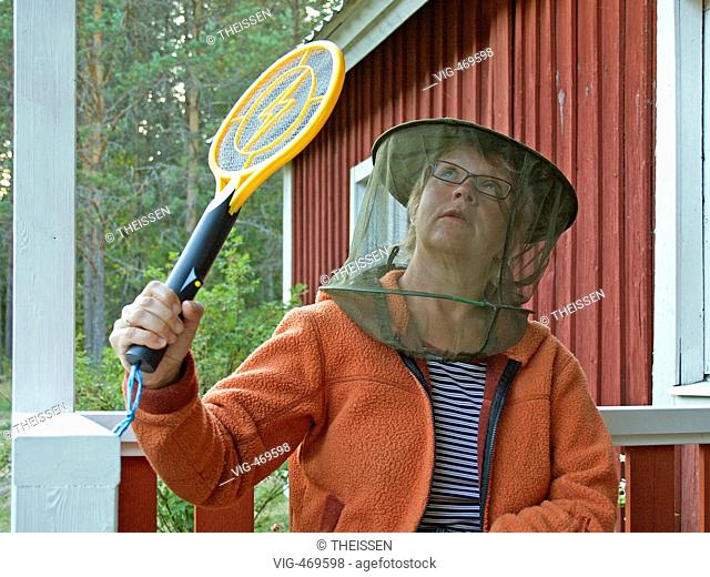 woman wearing a hat with gaze as protection against gnats mosquitos sitting in front of a red scandinavian timber wooden house trying to catch mosquitos with an...