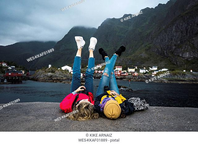 Norway, Lofoten, two young women lying on a pier at the coast