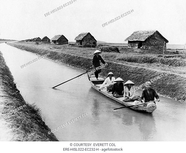 Vietnamese men in a sampan on a canal near straw dwellings that house refugees from North Vietnam. 1956. LC-DIG-ppmsca-09168