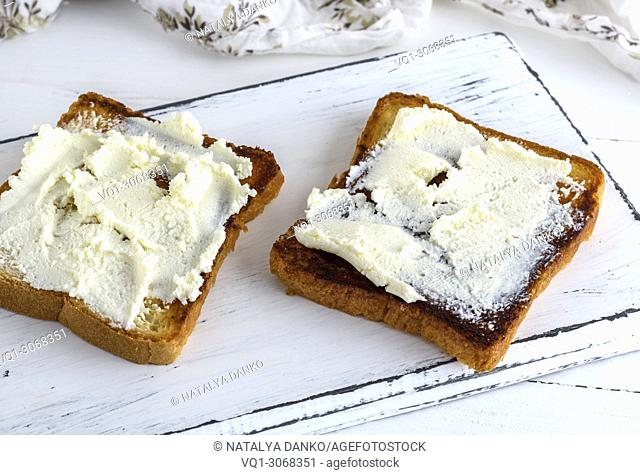 toasted bread with soft curd on a white wooden board, top view