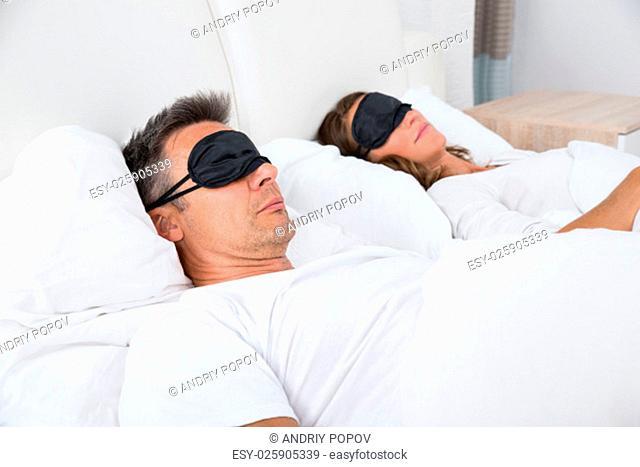 Portrait Of Matured Couple Sleeping Comfortably On Bed Using Eye Mask