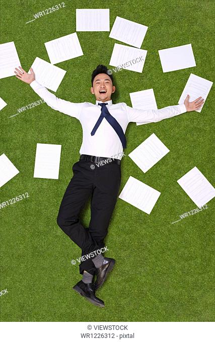 Young man lying on grass with sheets of paper