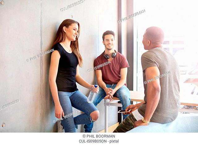 Three young male and female students chatting together at higher education college