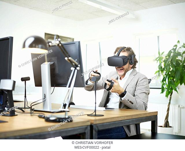 Happy man wearing VR glasses at desk in office