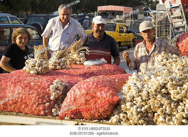 Stallholder selling garlic at weekly market standing behind stall piled with sacks of garlic bulbs in late afternoon summer sunshine