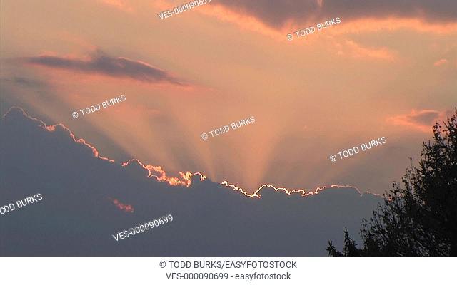 Time lapse of rain bearing clouds reflecting beautiful rays of sunlight at sunset