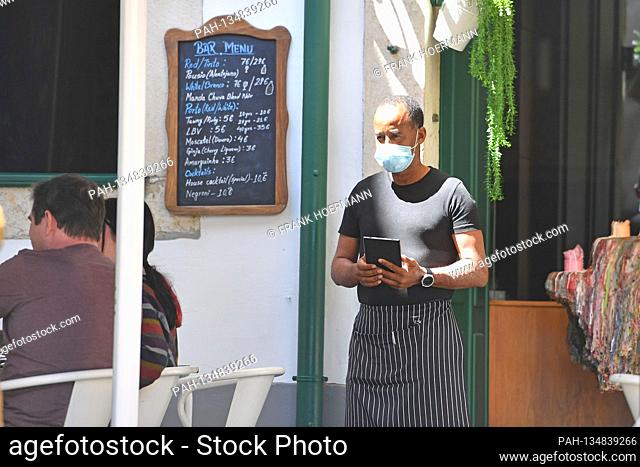 A waiter with face mask, mask waits for guests in front of the restaurant, gastronomy. In Portugal, the tourism industry is suffering massively from the...