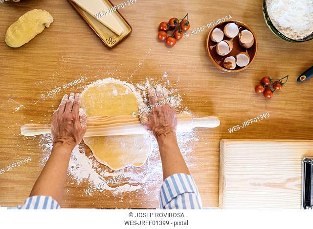 Woman preparing dough for ravioli, top view