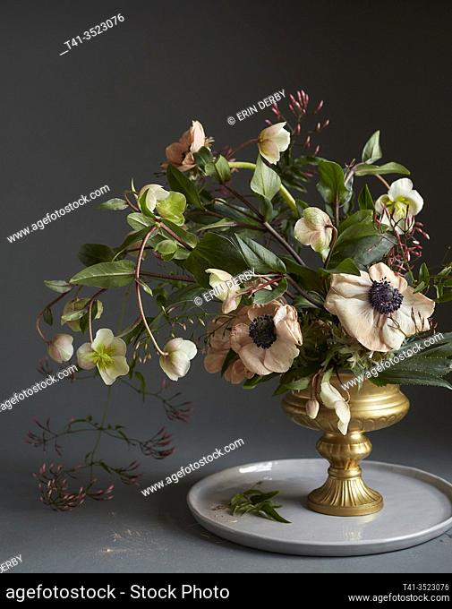 A romantic still life of a bouquet of flowers, including anemone and hellebore
