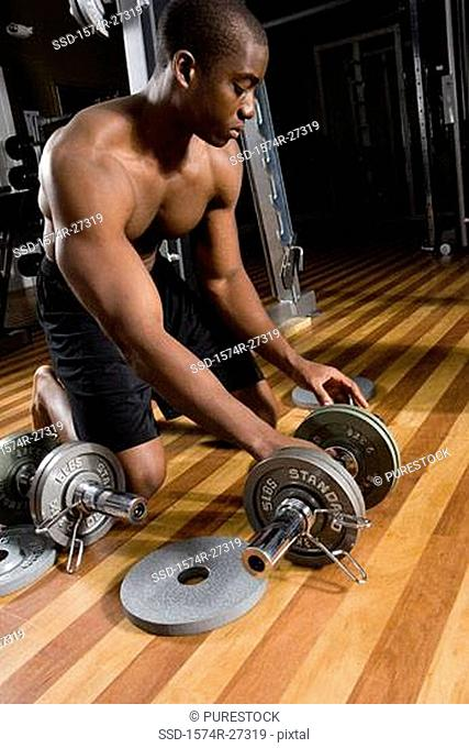 Young man holding dumbbells in the gym