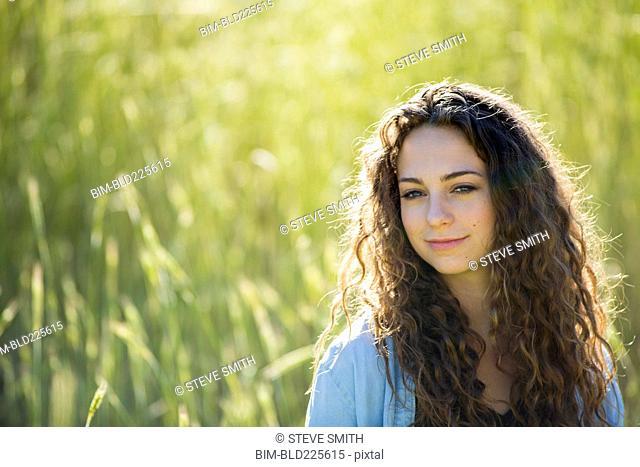 Caucasian woman standing in field of tall grass
