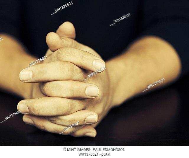 The clasped hands of a man wearing dark coloured clothes