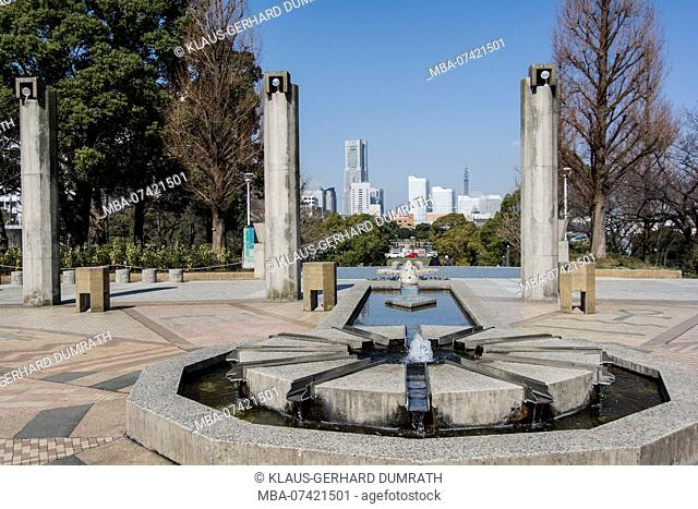 Yamashita Park with steles, fountain and city panorama of Yokohama in Japan