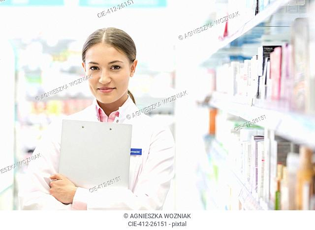 Portrait of confident pharmacist holding clipboard in pharmacy