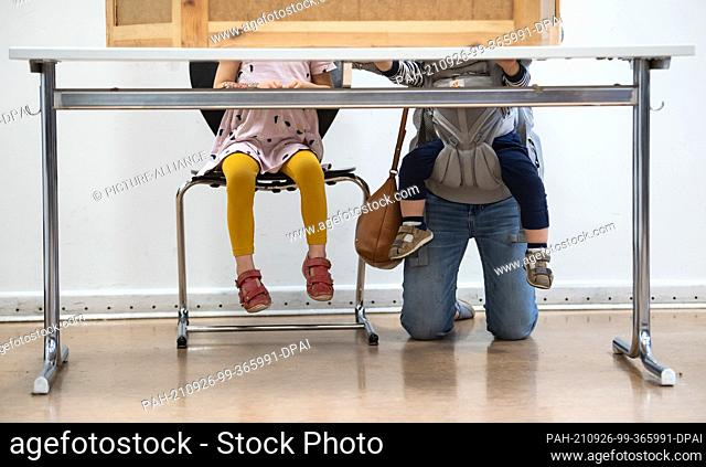 dpatop - 26 September 2021, Berlin: A young mother with two children kneels behind the voting booth at the Jane Addams School in Friedrichshain and fills out...