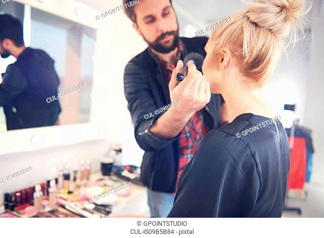 Male make up artist applying blusher to model for photo shoot