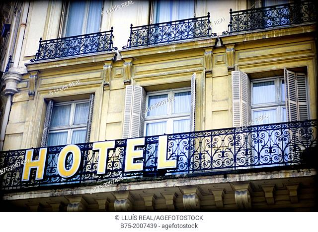 Classical architecture facade with balconies with a sign of hotel in the center of Paris, France, Europe