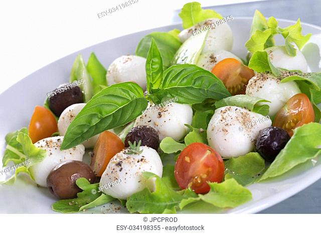 salad with mozzarella, tomatoes bloack olives and basil