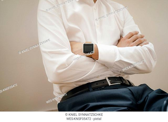 Mid section of a businessman wearing smartwatch with arms crossed
