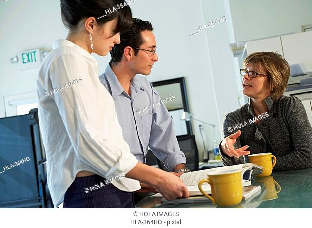 Two businesswomen and a businessman sitting in an office