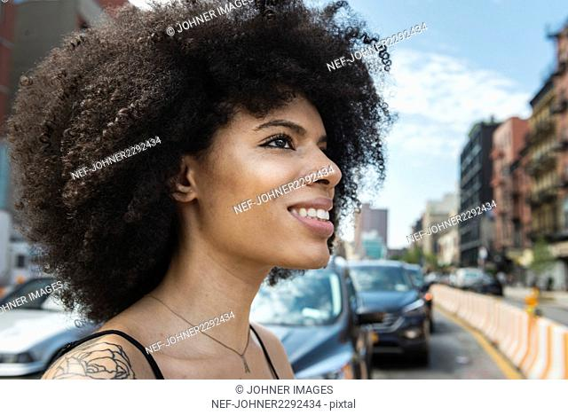 Smiling woman looking away in city
