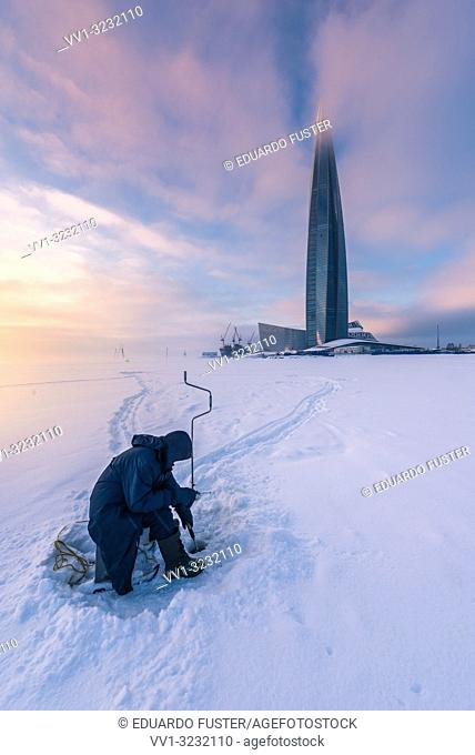 "SAINT PETERSBURG. RUSSIA - January 27 2019. Skyscraper """"Lakhta center"""" (Gazprom headquarters) twilight. Fisherman in a frozen sea during sunset"