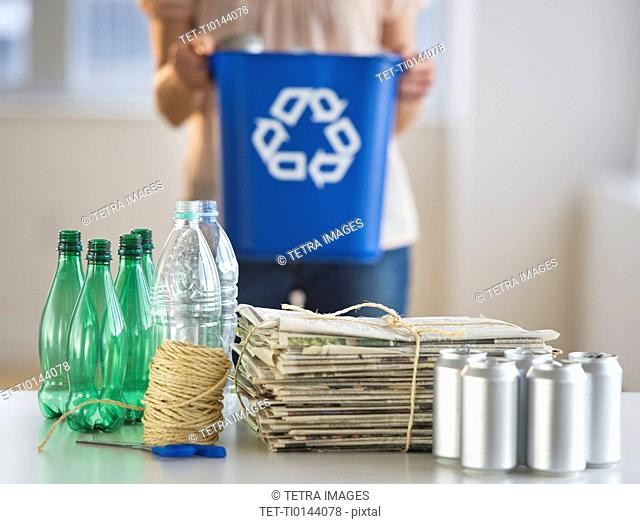 Woman recycling plastic bottles, cans and newspapers
