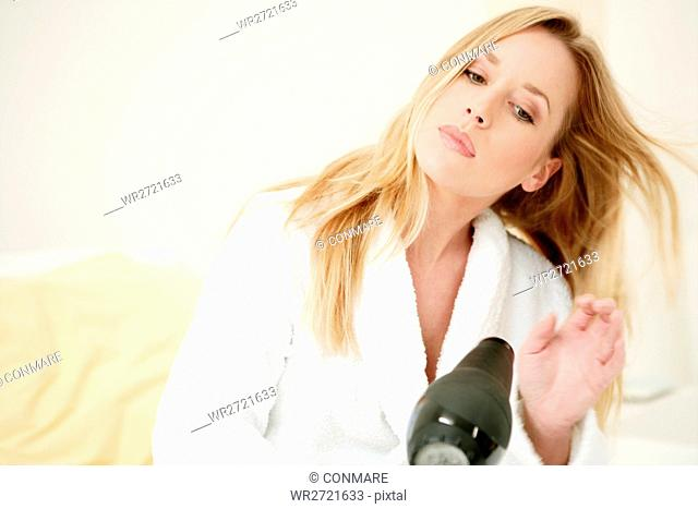young, woman, sitting, bed, blow, drying, hair, mo