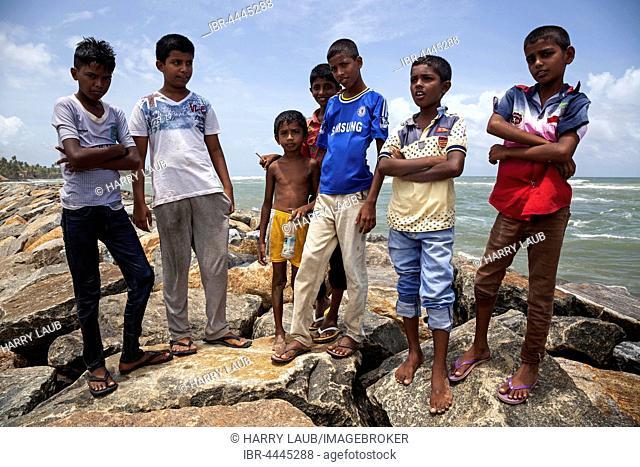 Local children on breakwater in harbour, Beruwela, Western Province, Sri Lanka