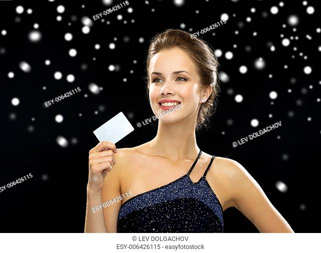 wealth, money, luxury and people concept - smiling woman in evening dress holding credit card over black snowy background