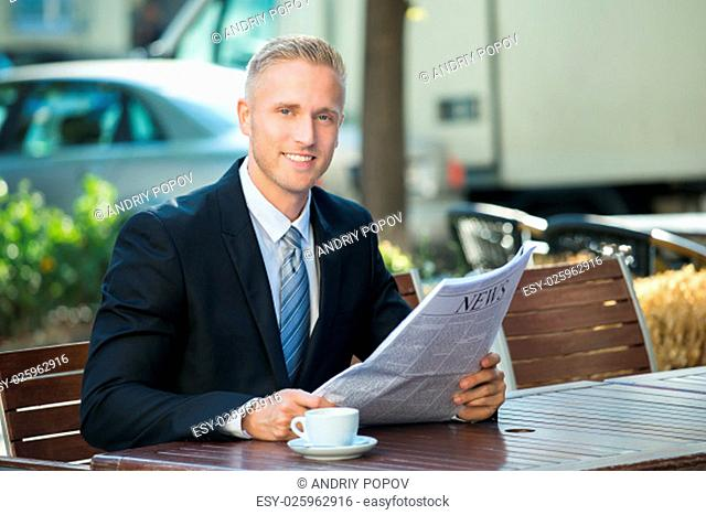Photo Of Businessman Sitting In Cafe Reading Newspaper