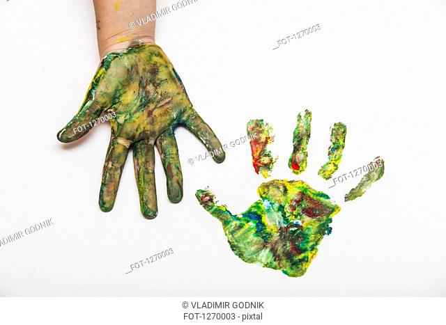Child with colorful painted hand beside her hand print on paper