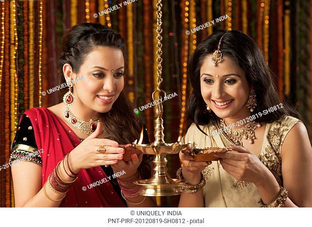 Female friends burning oil lamps on Diwali