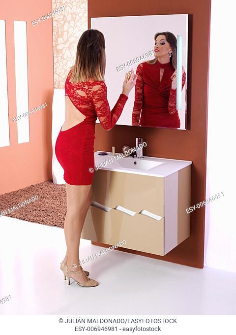 Perfuming beautiful young woman in the bathroom