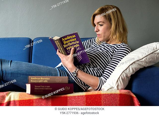 Tilburg, Netherlands. Young adult caucasian woman reading a book, while stretched out on her couch