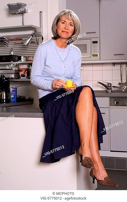 Eine aeltere Frau mit grauen Haaren sitzt in der Kueche, Hamburg 2006 - Hamburg, Germany, 16/01/2006