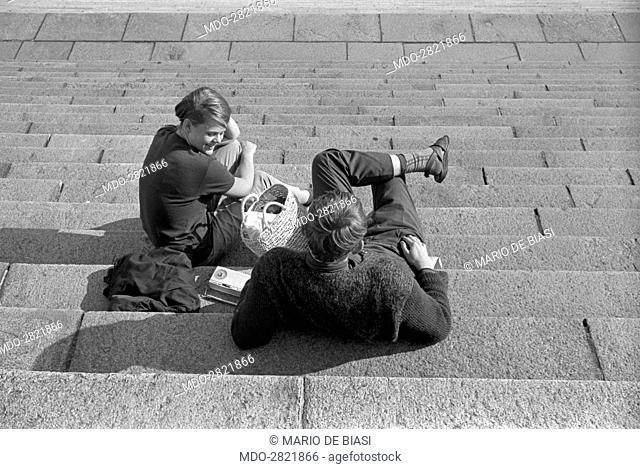 Two young people chatting on a staircase. Finland, 1960s