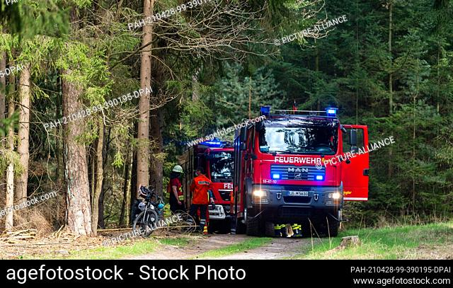 28 April 2021, Lower Saxony, Melbeck: Emergency vehicles of the fire brigade stand in the forest near a fire site. By chance
